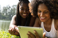 Afro Women Using Tablet Computer In The Park Stock Images - 69568014