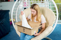 Girl Sitting In Chair And Opening A Package Stock Photography - 69609262
