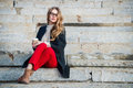 Beautiful Girl With Coffee Cup Sitting On Outdoors Stairs Wearing Red Pants And Glasses. Royalty Free Stock Photos - 69756428