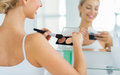 Woman With Makeup Brush And Foundation At Bathroom Stock Photo - 69781200