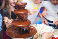 Vibrant Picture Of Chocolate Fountain Fontain On Childen Kids Birthday Party With A Kids Playing Around And Marshmallows And Fruit Stock Images - 69906514