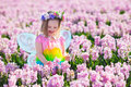 Little Girl In Fairy Costume Playing In Flower Field Stock Photos - 69910683