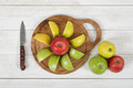 Ripe Juicy Apples Lie On Wooden Board With A Knife Next To It In Top View Royalty Free Stock Photography - 69952977