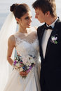 Beautiful Couple. Gorgeous Bride In Wedding Dress Posing With Elegant Groom On Sea Cost Stock Photos - 69969153