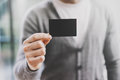 Man Wearing Casual Shirt And Showing Blank Black Business Card. Blurred Background. Horizontal Mockup Stock Photo - 70103250