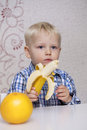 Beautiful Little Baby Boy Eats Banana Royalty Free Stock Images - 70313029