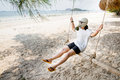 Girl With Gas Masks Sitting On Swing At The Sea,  Concept On The Royalty Free Stock Photo - 70429255
