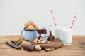 Chocolate Brownie Slices Wrapped In Paper And Tired With Rope, Milk Glasses, Stripe Straws, Enamel Mug Of Walnuts On Stock Photos - 70542853