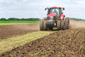 Modern Tech Red Tractor Plowing A Green Agricultural Field In Spring On The Farm. Harvester Sowing Wheat. Stock Photography - 70654002