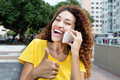 Mexican Girl At Phone Showing Thumb Outdoor In City Royalty Free Stock Photos - 70656758