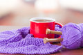 Closeup Purple Yarn Ball With Knitting Needles And Scarf In Progress Lying On Desk, Coffee Mug Sitting Next To It Royalty Free Stock Images - 70685029
