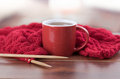Closeup Red Yarn Ball With Knitting Needles And Scarf In Progress Lying On Desk, Coffee Mug Sitting Next To It, Blurry Royalty Free Stock Photo - 70685035