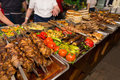 Customers Choosing Meat And Vegetables From Buffet Stock Photography - 70739252