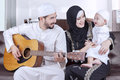 Joyful Middle Eastern Family Playing Guitar Royalty Free Stock Photography - 70745947