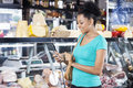Woman Using Cell Phone In Grocery Shop Stock Image - 70780831