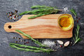 Wooden Cutting Board, Olive Oil, Rosemary Plant, Salt, Garlic And Pepper On Black Table From Above For Food Cooking Background Or Royalty Free Stock Photos - 70821118