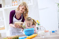 Smiling Beautiful Mom With Child Putting Flour Royalty Free Stock Photography - 70925697