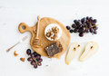 Camembert Cheese With Grape, Walnuts, Pear And Honey On Oak Serving Board Royalty Free Stock Image - 70938996