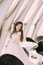 Charming Bride In White Dress And With Curly Hairstyle Posing Near Window At Cafe Stock Photography - 70958272
