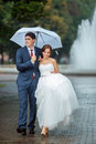 Happy Bride And Groom At Wedding Walk White Umbrella Royalty Free Stock Images - 71191239