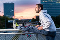 Runner Stretching In Front Of Office Building At Sunset Royalty Free Stock Photo - 71284285