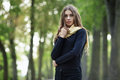 Outdoor Portrait Of Young Beautiful Brunette Woman With Wavy Long Hair Stares Into Camera Posing On The Park With Blurry Forest Ba Stock Image - 71310591