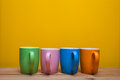 Colorful Coffee Cups On Wooden Table Over Yellow Background Royalty Free Stock Photos - 71350278
