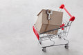 Shopping Cart With Model Of Cardboard House On Gray Background, Buying A New Home Or Sale Of Real Estate Concept Royalty Free Stock Photo - 71508405