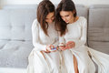 Two Sisters Twins Sitting On Couch And Using Mobile Phones Stock Images - 71510014