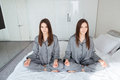 Two Sisters Twins Practicing Yoga And Meditating On Bed Royalty Free Stock Photo - 71510055