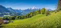 Idyllic Alpine Landscape With Green Meadows, Farmhouses And Snow-capped Mountain Tops Royalty Free Stock Photo - 71522575