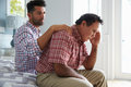 Adult Son Comforting Father Suffering With Dementia Royalty Free Stock Photos - 71524288