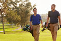 Two Male Golfers Walking Along Fairway Carrying Bags Royalty Free Stock Photos - 71525638