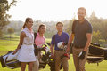 Group Of Golfers Walking Along Fairway Carrying Golf Bags Stock Photography - 71526362