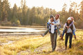 Parents Giving Children Piggyback Ride On Walk By Lake Stock Photography - 71529832