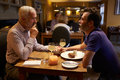 Middle Aged Male Couple Having Evening Meal In A Restaurant Stock Photos - 71533513