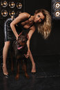 Beauty And Fashion. Woman With Gorgeous Curly Hair Embraces The Doberman. Dark Background, The Girl Next Door With A Dog Royalty Free Stock Photography - 71563497