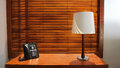 Wooden Table With Lamp And Telephone With Wooden Shutters In Background Stock Photos - 71589403