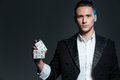 Serious Young Man Magician Standing And Holding Two Playing Cards Stock Photos - 71665713