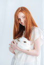 Smiling Redhead Woman Holding Rabbit Stock Photo - 71707510