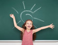 Schoolgirl Child In Red Striped Dress Drawing Sun On Green Chalkboard Background, Summer School Vacation Concept Stock Images - 71794524