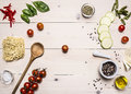 Ingredients For Cooking Vegetarian Food, Cherry Tomatoes, Basil, Zucchini, Mortar Pepper, Oil, Wooden Spoon, Laid Out On A White W Royalty Free Stock Photography - 71872917
