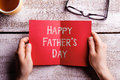 Fathers Day Composition. Hands Of Dad Holding Greeting Card Stock Photos - 71923543