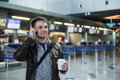 Portrait Of Young Handsome Man Walking In Modern Airport Terminal, Talking Smart Phone, Travelling With Bag And Coffee Royalty Free Stock Photos - 72032358