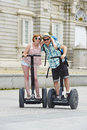 Young Happy Tourist Couple Riding Segway Enjoying City Tour In Madrid Palace In Spain Having Fun Driving Together Stock Images - 72239384