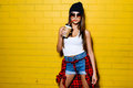Beautiful Young Sexy Girl Drink Coffee, Smiling And Posing Near Yellow Wall Background In Sunglasses, Red Plaid Shirt. Stock Images - 72326434