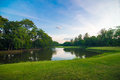 Green Grass In Public Park With Pond Background. Royalty Free Stock Photo - 72349735