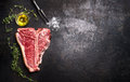 Raw T-bone Steak With Fresh Herbs And Oil On Dark Rust Metal Background, Top View Stock Image - 72396461