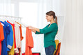 Happy Woman With Shopping Bags And Clothes At Home Royalty Free Stock Images - 72407699