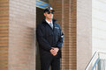 Male Security Guard Standing At The Entrance Royalty Free Stock Photo - 72445815